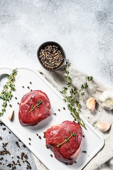 Raw filet mignon steak on a white chopping board. beef tenderloin. gray background. top view. space for text