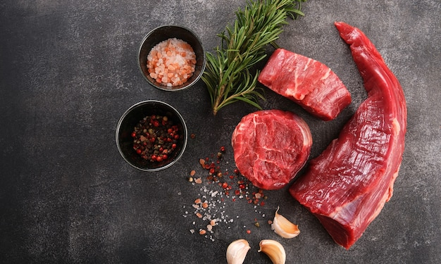 Raw filet mignon steaks with herbs and spices, raw fresh marbled meat steak, top view.