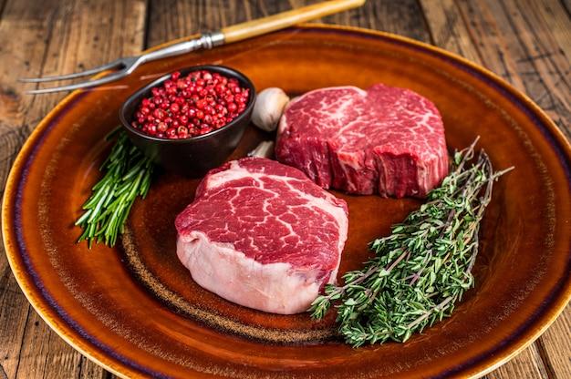 소박한 접시에 생 필레 미뇽 안심 고기 쇠고기 스테이크. 나무 배경입니다. 평면도.