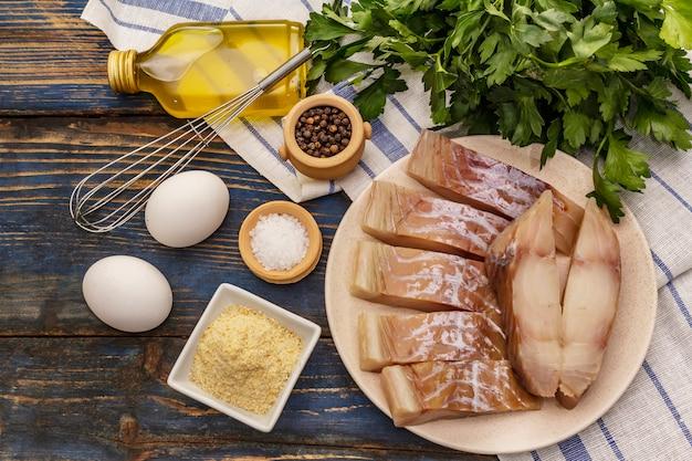 Saithe와 튀김 성분의 생 등심. 접시, 향신료, 계란, 기름, 빵 부스러기, 파 슬 리에 신선한 조각
