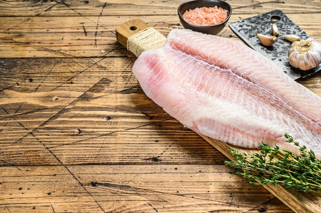 Raw fillet of pangasius fish on a cutting board. wooden background. top view. copy space.