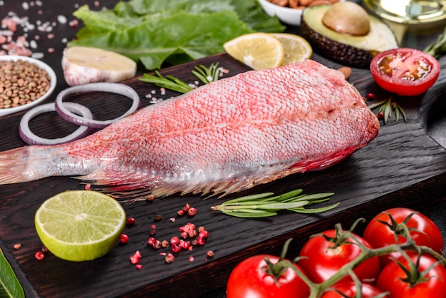 Raw fillet of red sea perch prepared for baking with spices and herbs