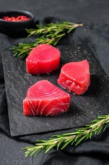 Raw fillet steak tuna. black wall. top view
