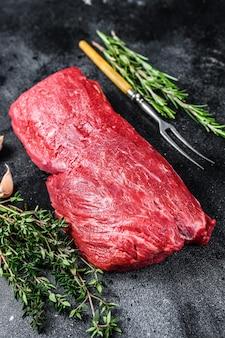 Сырое филе вырезка из говядины для стейков с тимьяном и розмарином. черный фон. вид сверху.