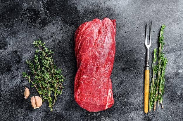 Сырое филе вырезка из говядины для стейков с тимьяном и розмарином.