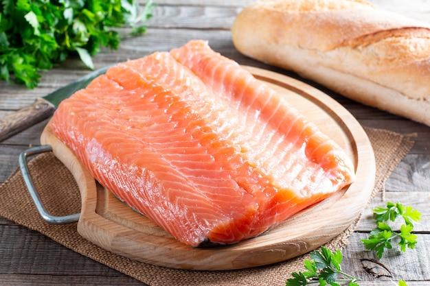 Сырое филе красной рыбы на деревянном столе, лосось, приготовление здоровых диетических блюд на ужин