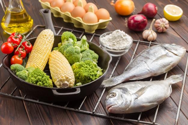 Сырая рыба и сковорода с овощами на гриле