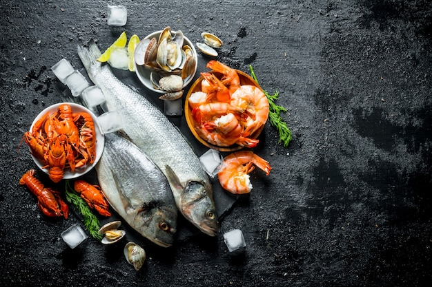 Сырая рыба и морепродукты на каменной доске с кубиками льда и дольками лайма.