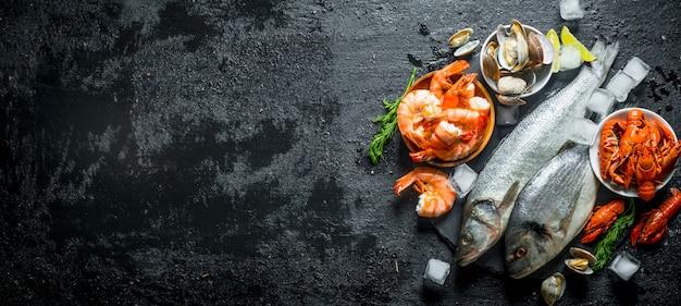 Сырая рыба и морепродукты на каменной доске с кубиками льда и ломтиками лайма на черном деревенском столе