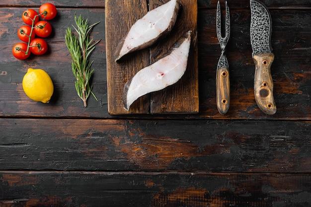 古い暗い木製のテーブルの背景に、食材とローズマリーハーブを含む生の魚のカットセット、上面図フラットレイ、テキスト用のコピースペース