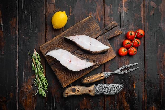 古い暗い木製のテーブルの背景に、食材とローズマリーハーブを含む生の魚のカットセット、上面図フラットレイ