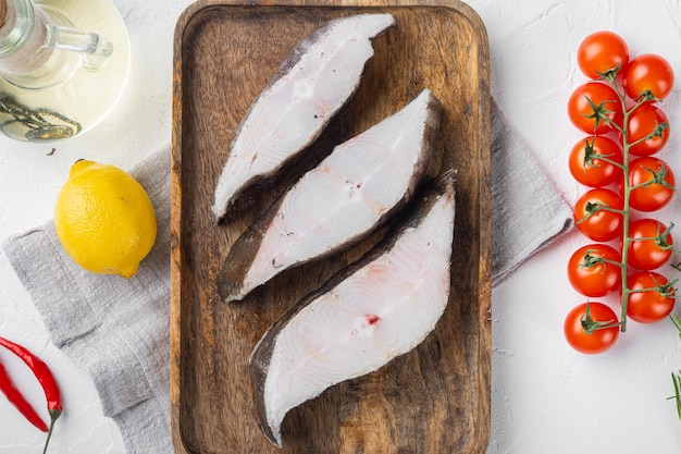 Набор для резки сырой рыбы, с ингредиентами и травами розмарина, на фоне белого каменного стола, плоская планировка, вид сверху