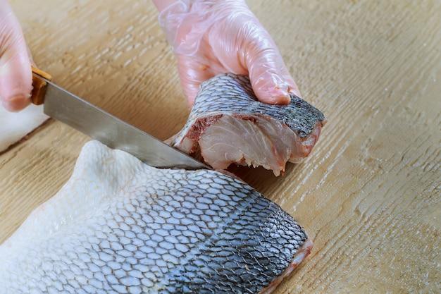 Raw fish. cutting fresh blyufish women's hands.