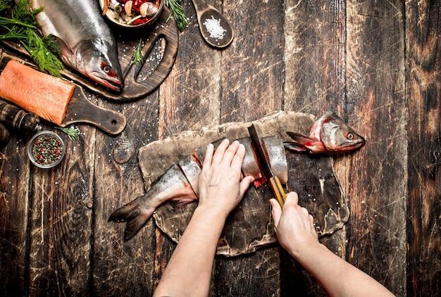 生の魚新鮮な鮭の女性の手を切る古い木製のテーブル