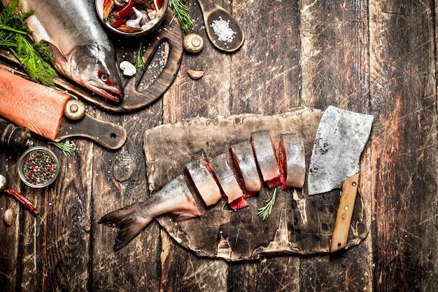 生の魚。新鮮な鮭の女性の手を切る。古い木製のテーブルの上。