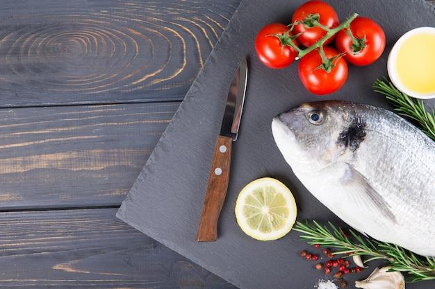 Сырая рыба приготовления дорадо и ингредиенты. дорадо, лимон, помидор, зелень и специи. вид сверху на деревянный стол