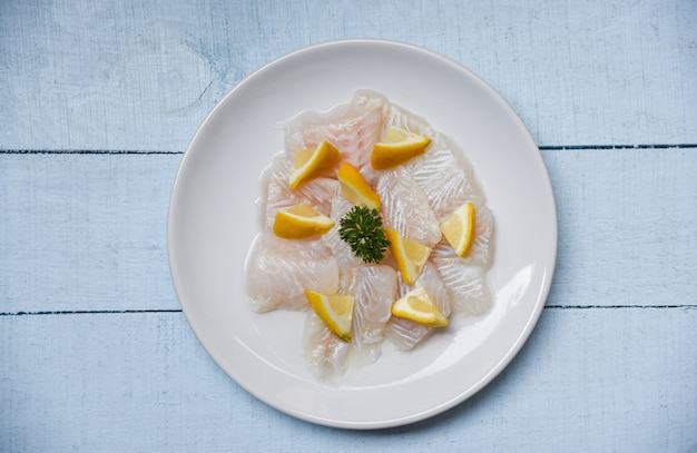 Raw fish fillet piece with lemon on white plate