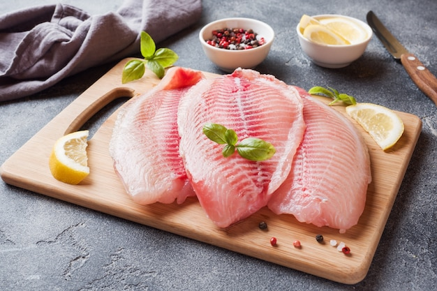 Raw fish fillet of tilapia on a cutting board with lemon and spices. dark table with .