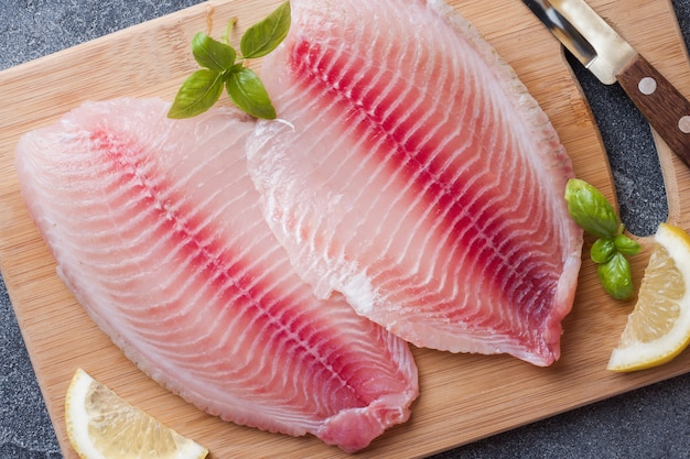 Raw fish fillet of tilapia on a cutting board with lemon and spices. dark table