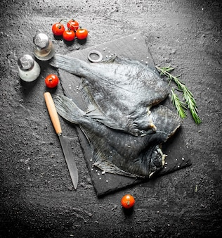 ナイフ、スパイス、トマトを添えた石板の生魚ヒラメ。黒の素朴な背景に
