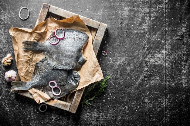 オニオンリングとニンニクのクローブが付いているトレイの生の魚のヒラメ。暗い素朴な背景に
