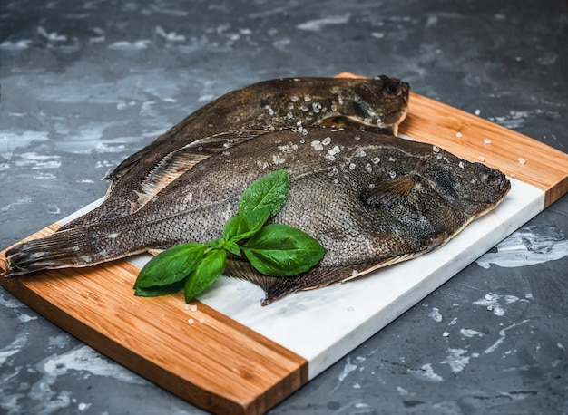 Raw fish flounder with salt and basil on a kitchen board closeup