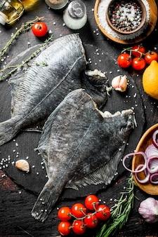 Raw fish flounder with spices, tomatoes, chopped onion and garlic