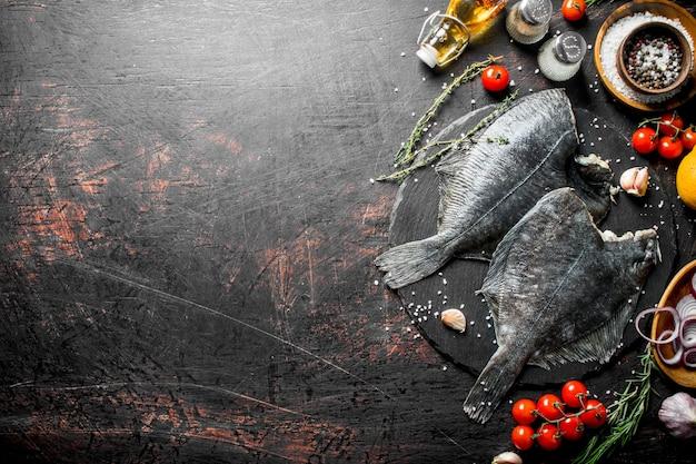 素朴なテーブルにスパイス、トマト、刻んだタマネギニンニクと生の魚のヒラメ