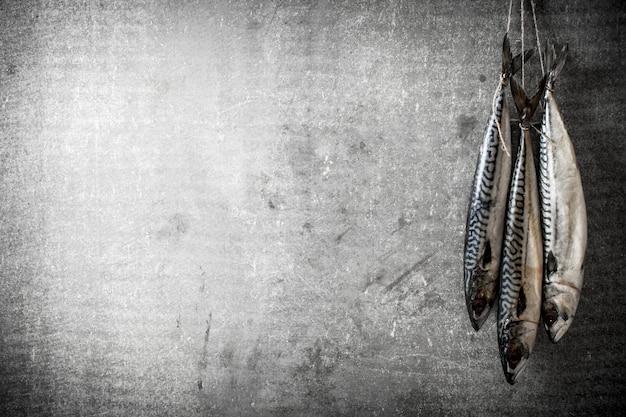 ロープにぶら下がっている生の魚。石の背景に。