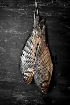 ロープにぶら下がっている生の魚。