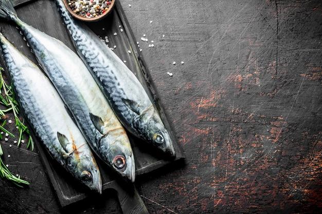 로즈마리와 향신료 커팅 보드에 생선 고등어. 어두운 소박한 표면에