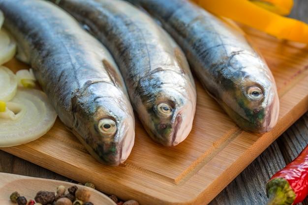 Сырая рыба на кухонном столе с ингредиентами для приготовления пищи Premium Фотографии