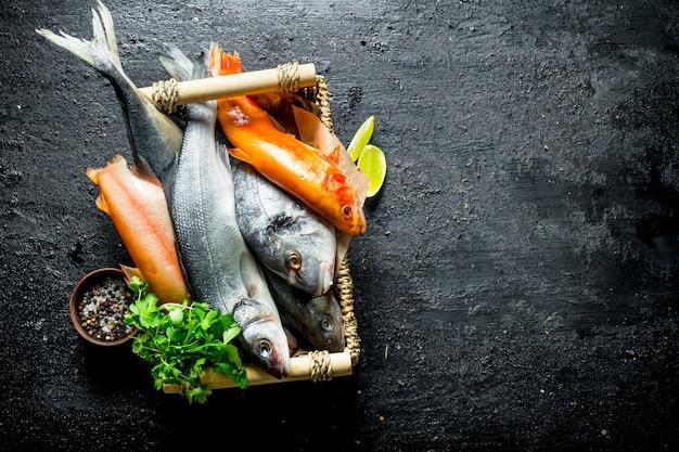 Сырая рыба на подносе с кусочками петрушки и лайма. на черном деревенском