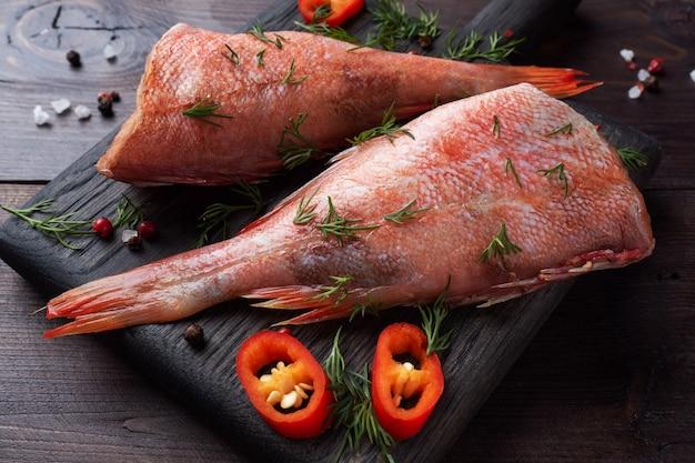 Сырая рыба окунь без головы с зеленью укропа на подставке