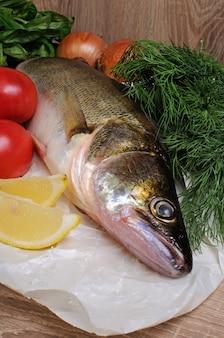 Сырая рыба судак на бумаге возле овощей