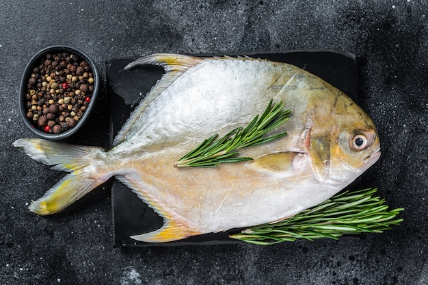 Помпано из сырой рыбы с травами на мраморной доске. черный фон. вид сверху.
