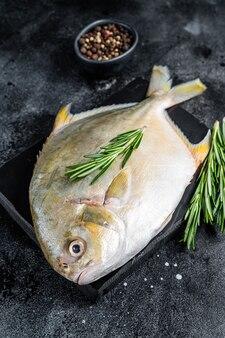 大理石のボードにハーブと生の魚のポンパーノ