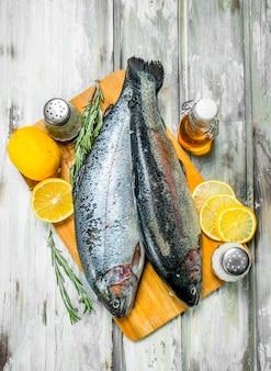 Лосось сырой рыбы с розмарином и лимоном. на деревенском фоне