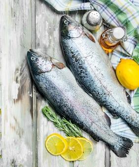Лосось сырой рыбы с розмарином и лимоном. на деревенском