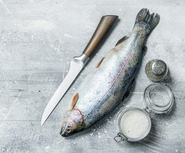 Лосось сырой рыбы с солью и перцем. на деревенском фоне.
