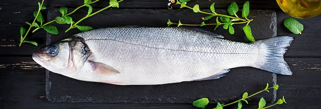 Raw fish. sea bass on slate blackboard. ingredients for cooking, grill, baked. copy space. banner. top view