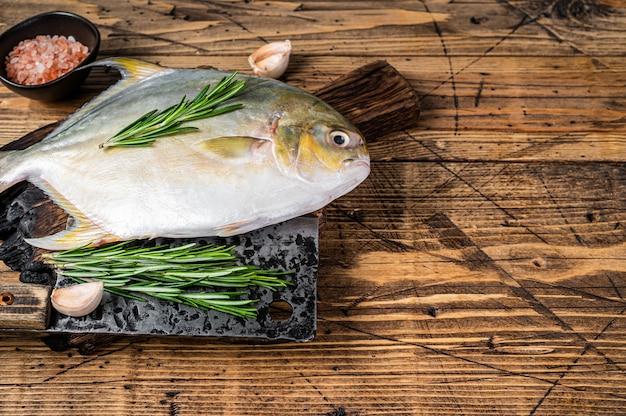 Сырая рыба санфиш или помпано на деревянной доске. деревянный фон. вид сверху. скопируйте пространство.