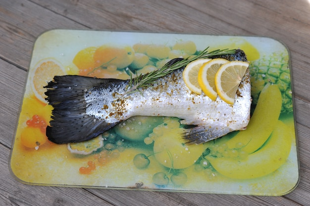 Raw fish tail salmon with lemon and rosemary