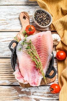 鍋に生の魚テラピア。白い木製の背景。上面図