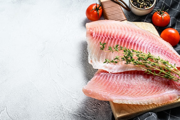 Raw fish tilapia on the cutting board. gray background. top view. copy space.