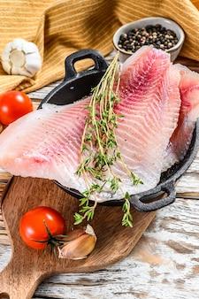 Сырая рыба тилапия на сковороде