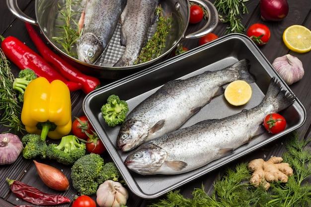 金属製のトレイに生の魚のマス。ローズマリーとレモンのくさびの小枝、赤唐辛子。暗い木の背景。上面図。