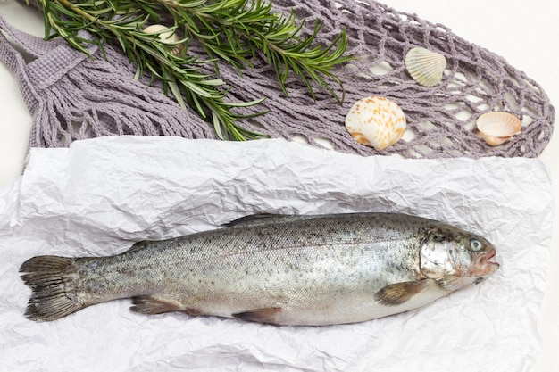 Raw fish trout on paper. sprigs of rosemary on mesh bag. white background.