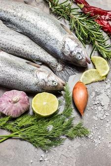 生の魚のマス。ローズマリーとレモンのくさびの小枝、赤唐辛子。金属のさびた背景。フラットレイ