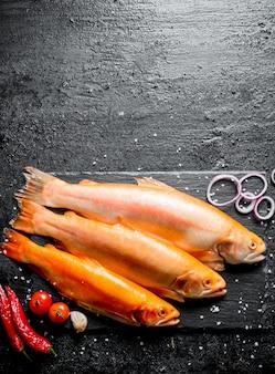 Форель сырая с перцем чили, помидорами и луковыми кольцами на черном деревенском столе